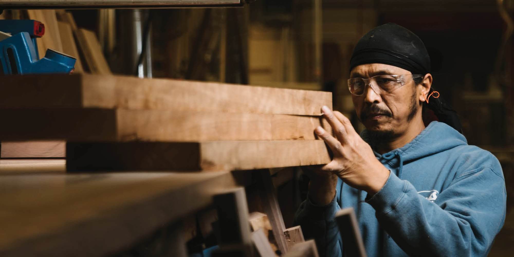 The Joinery crafts person inspecting Western Walnut lumber for the handcrafted furniture process